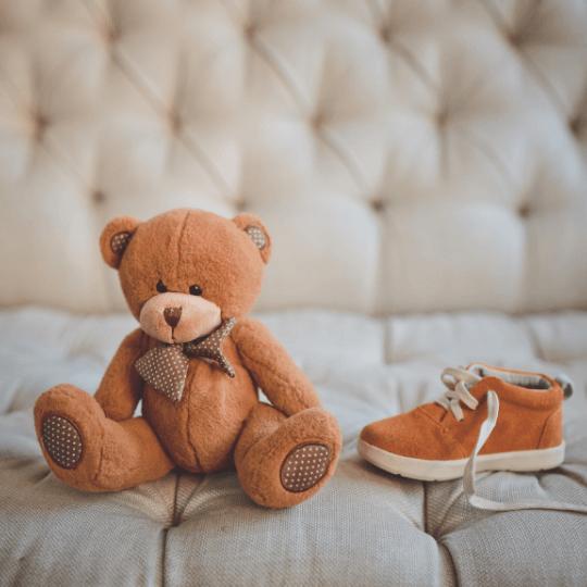 Kleinkinderschuhe in hellbraun neben einem Teddybären.